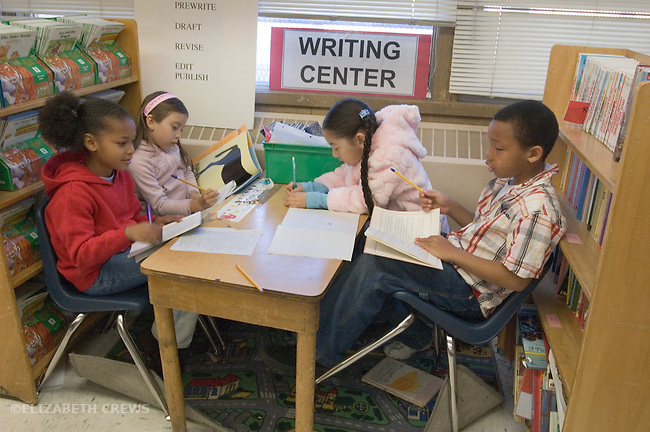Oakland CA 2nd graders working on writing projects in classroom Writing Center