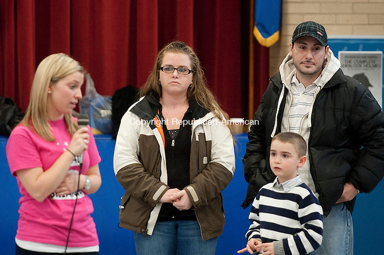 PROSPECT, CT-122013JS07-The parents of Brianna Pereira, a fourth grade student at Community School in Prospect, Misty, Victor and Camerin Pereira, 7, look on as Laura Naylor, a school psychologist, left, announces a donation to the family in the amount of  $21,406.77 to help with bills as Brianna battles cancer during a presentation Friday at the school. The money was raised through a Read-A-Thon as well as staff and community donations and was organized by Naylor and Britany Sweet.