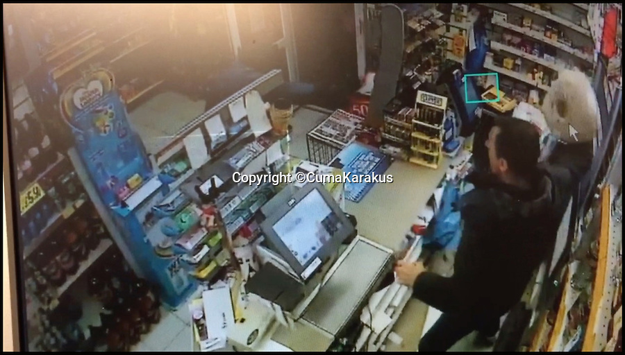 BNPS.co.uk (01202 558833)<br /> Pic: CumaKarakus/BNPS<br /> <br /> The moment Cuma picks up a ball of string.<br /> <br /> This is the dramatic movement a heroic shopkeeper scared off a knife-wielding raider by launching a glass jar of dog biscuits at him. <br /> <br /> Brave Cuma Karakus dodged the masked thug's eight inch blade as he jabbed over the counter armed only with the treats he keeps for customers' pets. <br /> <br /> The dad of two then incredibly threw it at the crook as he tried to run around the table, appearing to hit a glancing blow on his hand.