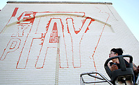 NWA Democrat-Gazette/DAVID GOTTSCHALK  Artist Olivia Trimble moves a lift into position to continue painting Friday, June 16, 2017, the logo for Experience Fayetteville on the backside the building on the square in downtown Fayetteville. Experience Fayetteville is the he city's tourism bureau. Trimble hoped to complete the large scale project Friday.