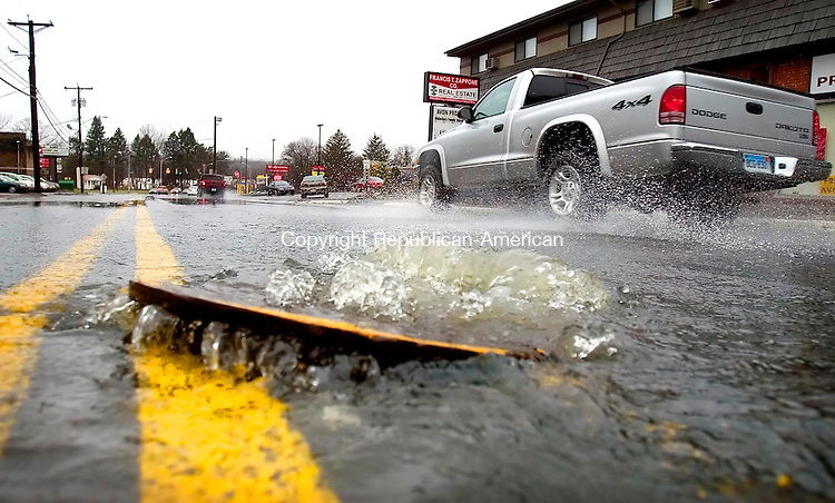 WATERBURY, CT. 16 April 2007-041607SV03--Water shoots up from a manhole cover on Meriden Road in Waterbury Monday. Water from an intense storm that flooded the area had no were else to go.<br /> Steven Valenti Republican-American