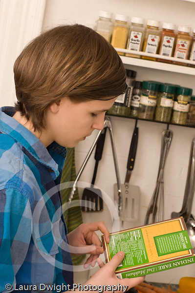 Teenage boy at home in kitchen food preparation reading directions or nutritional information on packaged food vertical Caucasian age 14