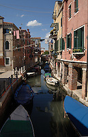 Buildings and boats reflected in water of canal in residential area of Venice. Venice, Italy.