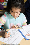 Education Elementary Grade 2 science specialist class girl writing at desk vertical