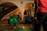 """Star actor and chairman of the Actors Guild of Nigeria Ajike Asiegbu ( center in green suit ) rehearses a scene supervised by director Charles Inoje ( on right with light color shirt ) on the set of a 21 episodes Nollywood Soap production called """"Close Shave""""  in Lagos, Nigeria on Saturday August 8 2009...Currently Nigerian films outsell Hollywood films in Nigeria and many other African countries. Nollywood is a nascent film industry in Nigeria, growing within the last two decades to become the third largest film industry on the planet, behind the United States and Indian film industries. Nigeria has a US$250 million movie industry, churning out some 200 movies for the home video market every month."""