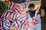 Apr. 19 2010 - BANGKOK, THAILAND: A woman sorts Thai flags in the back of a pickup truck before an anti-Red Shirt rally in the Silom financial district Monday. Hundreds of Thai soldiers, including reservists and front line units, and riot police moved into the Silom financial district Monday, not far from the red-shirts' main protest rally site, in Ratchaprasong. The heavy show of force is to prevent the Red Shirts from entering the Silom area. Many of soldiers were greeted as heros by workers in the area, who oppose the Red Shirts.   Photo by Jack Kurtz