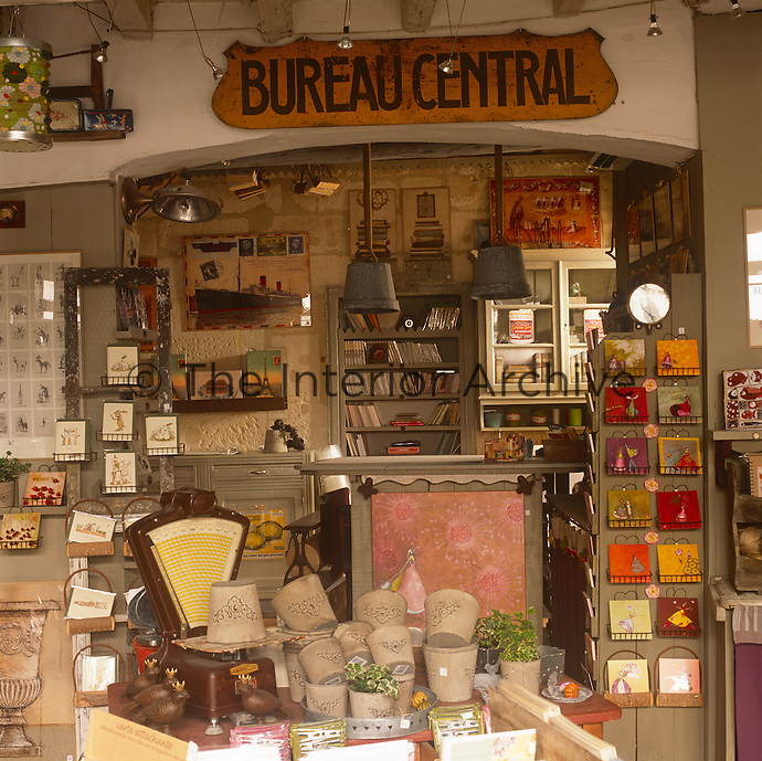 The interior of Noir et Blanc, a shop owned by Eric Pezzali situated in Saint Remy de Provence. The shop has a an eclectic selection of items including postcards, paintings, books and flower pots.