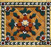One ceramic square of the 42-meter high Chedi of Rama I showing the detail and intricacy of the orange-based chedi decoration. The square is orange-based with a central rust and white flower surrounded by burgandy berries and dark green leaf design. The square's border if of dark green and white leaves and petals . Phra Maha Chedi Sri Sanpetdayarni is the chedi's formal title.