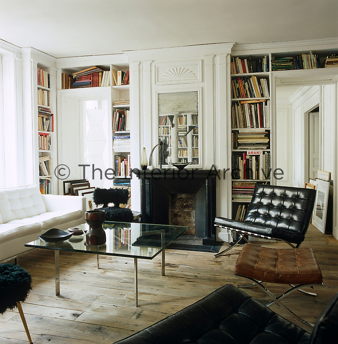 19th century wall panelling and bare floorboards rescued from a salvage yard provide a setting for 20th century furniture and Barcelona chairs