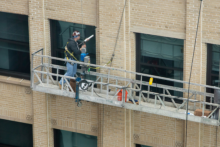 Workers replace windows on the east side of the Lewis Center building in the Loop campus Thursday, June 18, 2015. Each summer DePaul's Facility Operations department works tirelessly to build, renovate and otherwise spruce up DePaul's campuses before students return in the fall. (DePaul University/Jeff Carrion)