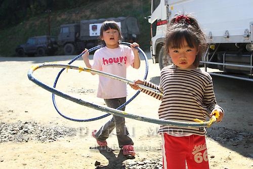 May 18, 2011; Minamisanriku, Miyagi Pref., Japan - 2;29 p.m. Ruka Sato (L), 5 and Sena Sato, 4, play with hula hoops at the Shizukawa High School Evacuation Center in Minamisanriku after the magnitude 9.0 Great East Japan Earthquake and Tsunami that devastated the Tohoku region of Japan on March 11, 2011.