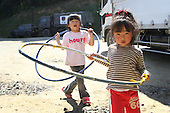 May 18, 2011; Minamisanriku, Miyagi Pref., Japan - 2;29 p.m. Ruka Sato (L), 5 and Sena Sato, 4, play with hula hoops at the Shizukawa High School Evacuation Center in Minamisanriku after the magnitude 9.0 Great East Japan Earthquake and Tsunami that devastated the Tohoku region of Japan on March 11, 2011.