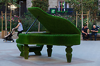 """Armenia. Yerevan. City center. A green ecological piano covered with grass. A mother and her child seated in a stroller. In the back, two men seated on a wooden bench and holding a mobile phone. The entrance to the Holiday Inn Express which is a mid-priced hotel chain within the InterContinental Hotels Group family of brands. Originally founded as an """"express"""" hotel, their focus is on offering limited services at a reasonable price. Standard amenities lean toward the convenient and practical which cater to business travelers and short-term stays. As of September 2019, there are 2,826 Holiday Inn Express hotels featuring over 292,000 rooms worldwide. The Holiday Inn Express concept was intended to target the """"upper economy"""" market segment, offering limited service, low-price lodging. The piano is an acoustic, stringed musical instrument invented in Italy by Bartolomeo Cristofori around the year 1700 in which the strings are struck by hammers. It is played using a keyboard, which is a row of keys (small levers) that the performer presses down or strikes with the fingers and thumbs of both hands to cause the hammers to strike the strings. Yerevan, sometimes spelled Erevan, is the capital and largest city of Armenia. 2.10.2019 © 2019 Didier Ruef"""