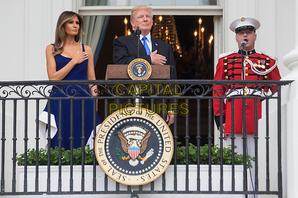 United States President Donald J. Trump and first lady Melania Trump observe the playing of the national anthem from the Truman Balcony on July 4, 2017 in Washington, DC. The president was hosting a picnic for military families  for the July 4 holiday.  <br /> CAP/MPI/RS<br /> &copy;RS/MPI/Capital Pictures