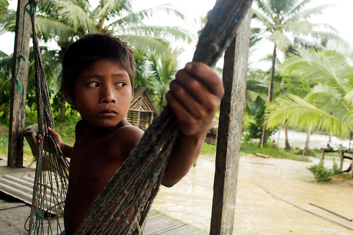 NUQUÍ, EL CHOCO, COLOMBIA -- DECEMBER 14: A young indigenous boy sits in his hammock in a small village near the town of Nuqui on December 14, 2005.   Nuquí is a small town on Colombia's isolated and untamed Pacific coast, an area sandwiched between endless miles of trackless rainforest and the Pacific Ocean. (Photo by Dennis Drenner/Aurora).