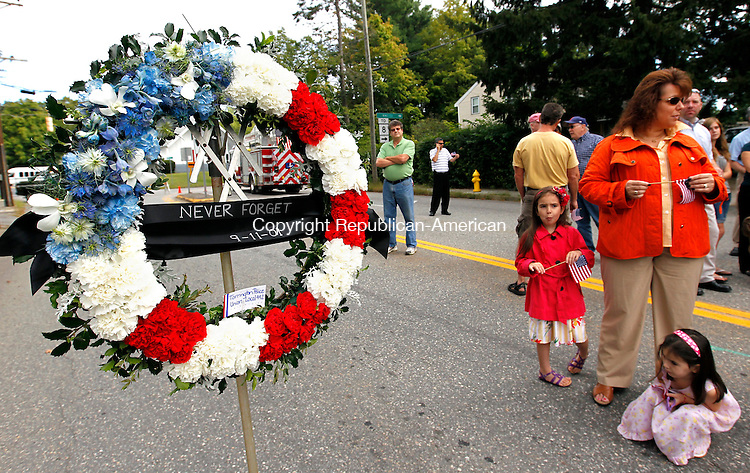 Torrington, CT- 11, September 2011-091111CM02 People come to pay tribute by gathering next to a memorial wreath before start of the 9/11 Memorial Service at the North End Fire Station in Torrington Sunday morning.   A piece of steel beam from the World Trade Center North Lobby was unveiled and will be displayed  in a memorial outside of the fire station.  Christopher Massa Republican-American