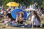 © Joel Goodman - 07973 332324 . 19/07/2013 . Suffolk , UK . Women shade themselves from the bright sunshine beneath parasols . The Latitude music and culture festival in Henham Park , Southwold . Photo credit : Joel Goodman