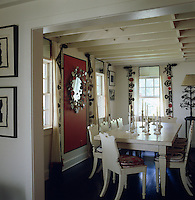 Marian McEvoy has artfully applied fragments of antique Suzani textiles to muslin panels to create unique curtain in this dining room