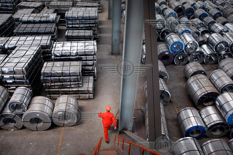 A worker walks down a flight of stairs onto a floor stocked with steel products at a warehouse run by the Shanghai Yirong Trading Company.