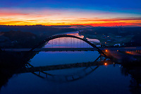 This aerial image was taken during a freezing cold December morning. The vibrant red, yellow and orange hues paint the blue sky over the iconic 360 Pennybacker Bridge over Lake Austin.