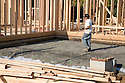 A construction worker laying steel rods where a concrete slab will be laid as part of this residential home project. Cupertino, California, USA