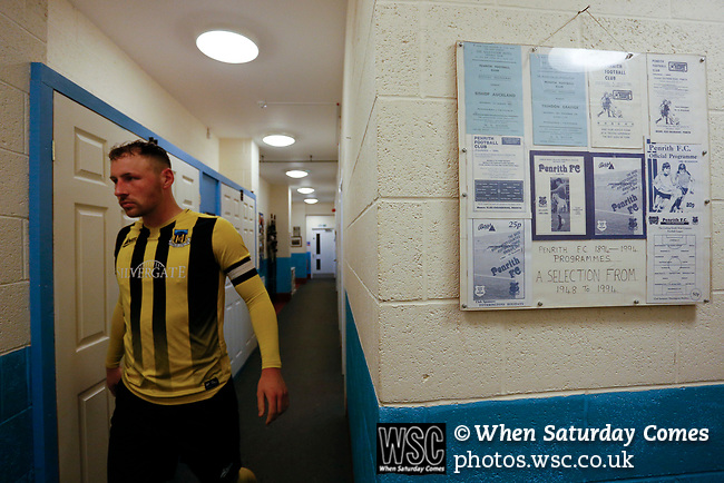 Hebburn's Loius Storey emerges for the second half, next to a selection of framed Penrith programmes. Penrith AFC V Hebburn Town, Northern League Division One, 22nd December 2018. Penrith are the only Cumbrian team in the Northern League. All the other teams are based across the Pennines in the north east.<br /> Penrith, winless at kick off, lost a thriller 3-4, in front of 100 people. They won five games all season, but were reprieved from relegation following Blyth's resignation from the league.