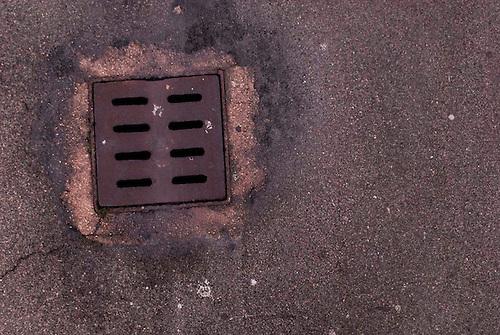 Taranto, Italie, Jan 2010. Bouche d'égout recouverte de rouille: les poussières de métaux s'infiltrent dans les réseaux d'eau. Tarente est la ville la plus polluée par émissions industrielles en Europe. A Tarente, chacun des 210 000 habitants respire chaque année 2,7 tonnes de monoxyde de carbone et 57,7 tonnes de dioxydes de carbones. Le quartier ouvrier de Tamburi, tout proche de la zone industrielle souffre très directement de la pollution industrielle.  Image issue de la Serie La Poussiere Rouge.