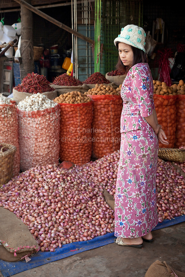Myanmar, Burma. Mandalay.  Woman in the Market.  Onions, Potatoes, Garlic, Peppers.
