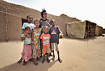 Back home in Timbuktu, Mali, after a year of living in the nation's capital, Bamako, Aissata Kantao poses with her five children in front of their home. They fled Timbuktu after the north of Mali was seized by Islamist fighters in 2012. They returned in 2013 several months after it was liberated by French and Malian soldiers, but Kantao hasn't found work in the war-torn city.