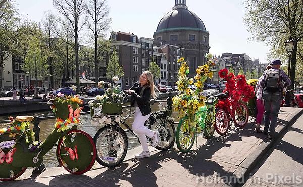 Nederland - Amsterdam - 2019.  Toeristen poseren bij de fietsen van de Flowerbikeman. Foto Berlinda van Dam Hollandse Hoogte