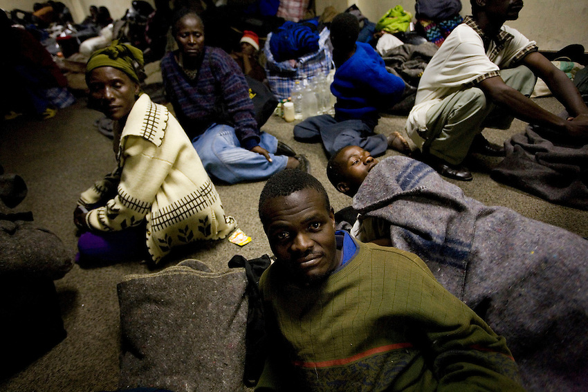 Victims of political violence during the Presidential run-off election in Zimbabwe take refuge at Harvest House, the MDC headquarters, in Harare, Zimbabwe, Monday, June 23, 2008. Due to a tip-off earlier in the day that police loyal to Robert Mugabe would raid the house, the majority of its more than 2,000 residents fled to avoid arrest. The headquarters was eventually raided at about noon that day and 60 MDC supporters, many of which were too old or injured to be evacuated, were arrested. Later in the night, when these images were taken, at least 700 of those who had fled had returned to escape the cold as they had nowhere else to go.