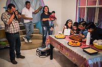 Carlos Saldaña (L)takes photos as he and other family members look on during a birthday party for their grandson, Hector Yael, 10, (R) blows out candle on his birthday cake, at a family gathering at Vicky's daughter, Cinthia Hernández Delgadilo's house in Xalapa, Mexico on November 4, 2017. <br /> Photo Daniel Berehulak for The New York Times