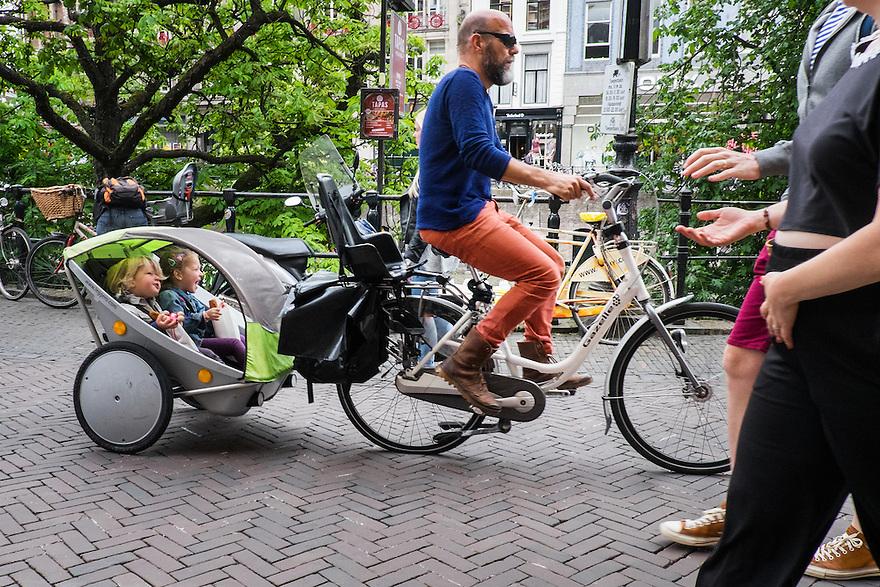 Nederland, Utrecht, 16 juni 2015 <br /> Vader met een fietskar met twee kinderen rijdt over de Oudegracht. Hij heeft zijn kinderen waarschijnlijk net van school gehaald. Fietskarren zijn een gewild vervoermiddel voor kleine kinderen.<br />  <br /> <br />  Foto: Michiel Wijnbergh