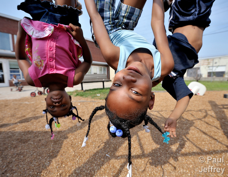 Children hang upside down while playing in a day care center run by the Lessie Bates Neighborhood House in East St. Louis, Illinois.
