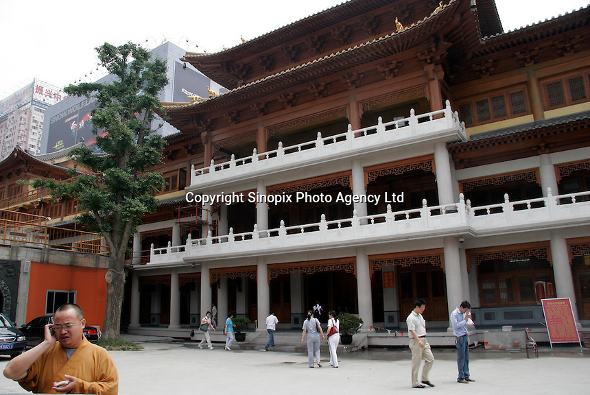 A Chinese Buddhist monk chats away on his cellphone at the Jin An Temple in downtown Shanghai, China..16 Jun 2005