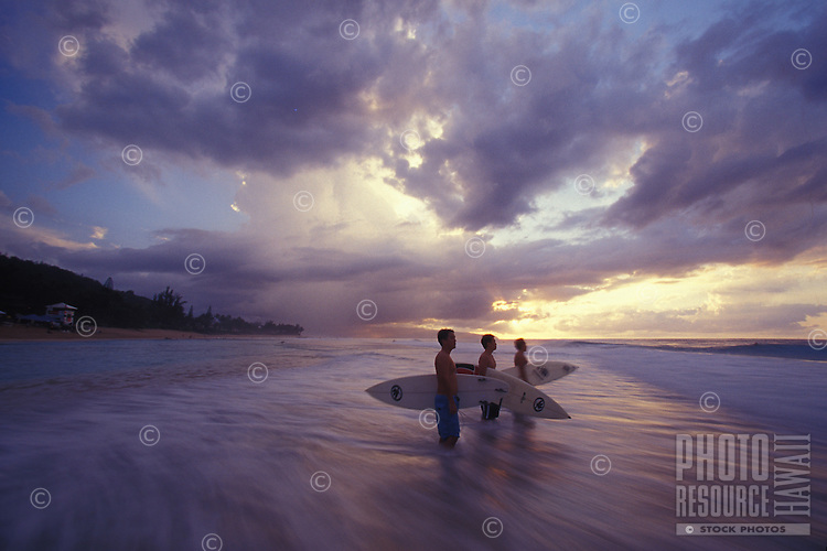 Surfers standing in water watching waves at sunset, Ehukai Beach, Pipeline, North Shore of Oahu
