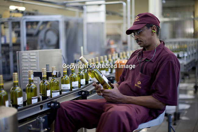 En arbetare kontrollera flaskor pa vingarden Bergkelder i Stellensbosch utanfor Kapstaden, Sydafrika. Foto: Per-Anders Pettersson
