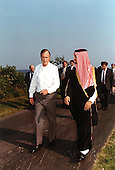 United States President George H.W. Bush walks along the driveway of his home in Kennebunkport, Maine with Foreign Minister Prince Saud Al-Faisal of Saudi Arabia on August 16, 1990.  They met to discuss the situation in the Persian Gulf.  National Security Advisor Brent Scowcroft can be seen behind the President at far left and White House Chief of Staff John Sununu can be seen behind the Prince at far right.  Prince Saud bin Faisal bin Abdulaziz Al Saud passed away of undisclosed causes on Thursday, July 9, 2015.<br /> Credit: White House via CNP