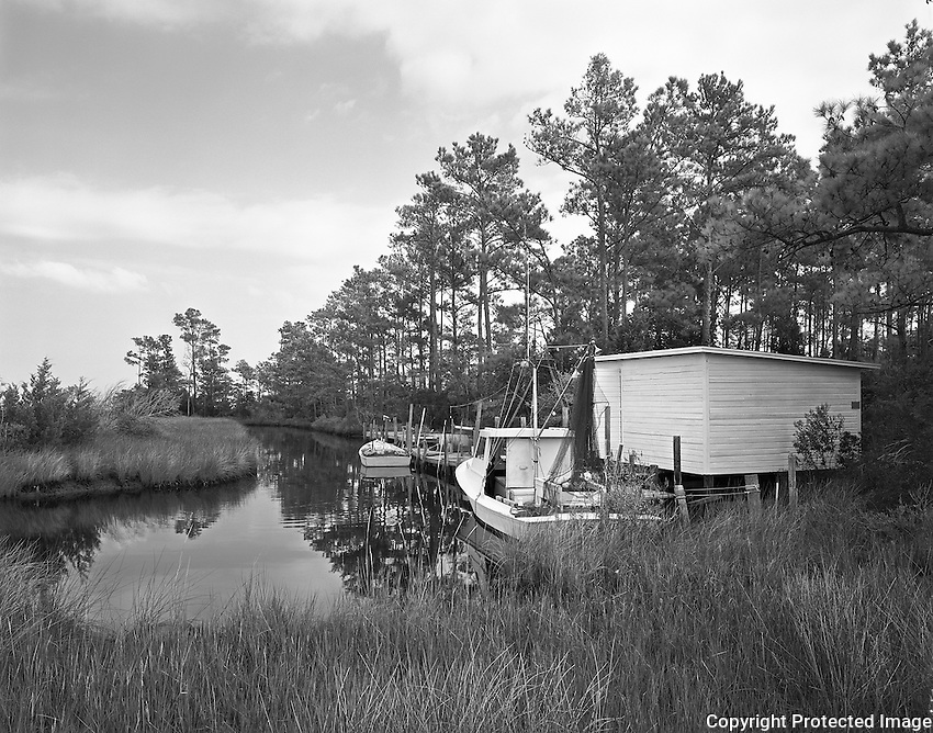 Calvin Rose, of Harkers Island, built the hull of the MISS SUE in 1962 for Monte Willis, of Stacy. At twenty-five feet in length, the boat can be handled easily by one person. Willis used her for shrimping, scalloping, and oystering. In the early 1970s, Leslie Hamilton, from Stacy, built the cabin, and in the late 1980s, fisherman Michael Braxton Fulcher, also from Stacy, bought the boat and renamed her MISS SUE for his wife. He added the pilot house after the boat's purchase.