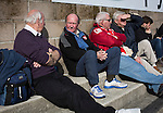 A group of home fans sitting in the sunshine on the terrace at the Globe Arena before Morecambe hosted Plymouth Argyle in a League 2 fixture. The stadium was opened in 2010 and replaced Morecambe's traditional home of Christie Park which had been their home since 1921, the year after their foundation. Plymouth won this fixture by 2-0 watched by 2,081 spectators, in a game delayed by 30 minutes due to traffic congestion affecting travelling Argyle fans.
