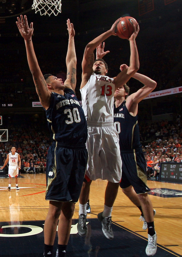 Virginia forward Anthony Gill (13) shoots next to Notre Dame forward Zach Auguste (30) during the game Saturday, February 22, 2014,  in Charlottesville, VA. Virginia won 70-49.