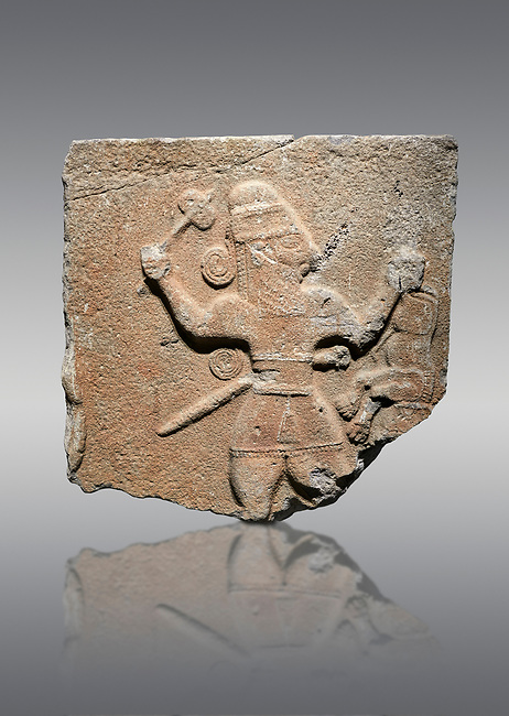 Hittite monumental relief sculpture of a man with an axe in one hand about to use it to kill a lion he is holding updide down in his other hand. Late Hittite Period - 900-700 BC. Adana Archaeology Museum, Turkey. Against a grey background