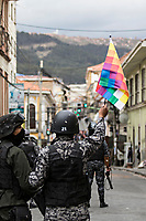 La Paz, Bolivia<br /> Wednesday November 13, 2019<br /> A police man shows a Whipala flag to people protesting near the Gobernment Palace in the Capital city of La Paz.  After the October 20 presidential elections and resignation of President Evo Morales, there is a lot of protests in many regions of Bolivia.