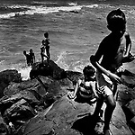 """Mumbai, the city symbolic of the Indian miracle and its sustained economic growth, will become, in 2020, the most populopus metropolis of the world. Today more than 40% of its inhabitants lives in the various slums and shantytowns that define the urban landscape of this Indian """"megacity""""Among the slums, the best known is Dharavi, thanks also to the international success of the Slumdog Millionaire movie. .Children swimming in the ocean May 15, 2007."""