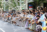 August 3, 2019, Tokyo, Japan - People dressed in yukata, summer kimono dress splash recycle water onto a ground a long a street at Ginza district in Tokyo for uchimizu event on Saturday, August 3, 2019. Hundreds of people participated in the event of splinkling water to cool down.   (Photo by Yoshio Tsunoda/AFLO)