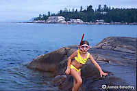 Little girl swimming with a snorkle and mask at the lake