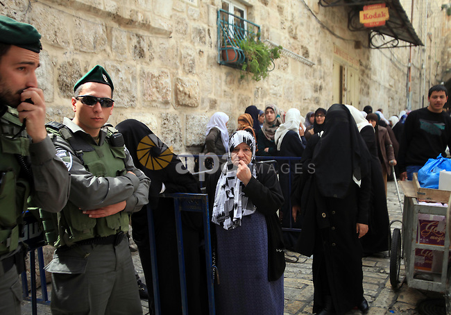 Palestinian protesters confront an Israeli policeman standing guard outside the entrance to al-Aqsa Mosque compound, Islam's third holiest site, in Jerusalem's old city on March 17, 2014, following disturbances that led to the temporary interruption of access into the Mosque. Photo by Saeed Qaq