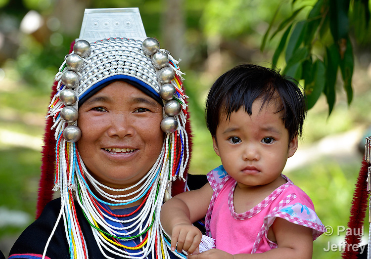 A traditionally dressed woman in Buyer, a small village in northern Thailand populated by indigenous hill tribe people, holds a small girl. The woman is a member of the local United Methodist congregation.