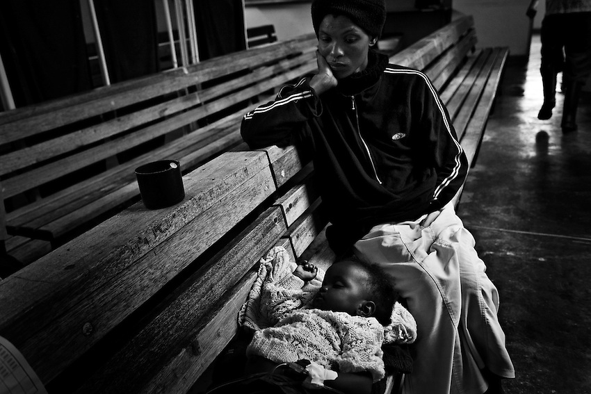 A Zimbabwean woman sits with her child, infected with cholera, while the child rehydrates through an IV at the Budiriro Polyclinic which is being used as a Cholera Treatment Clinic in Budiriro, Zimbabwe, Friday, December 19, 2008.