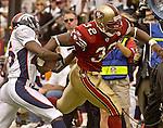 Denver Broncos defensive back Denard Walker (25) attempts to strip ball from San Francisco 49ers running back Kevan Barlow (32) on Sunday, September 15, 2002, in San Francisco, California. The Broncos defeated the 49ers 24-14.